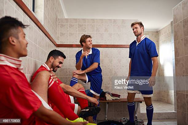 football teammates laughing in changing room - locker room stock pictures, royalty-free photos & images