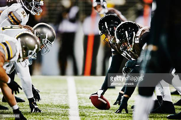 football teams on line of scrimmage in stadium - sports team event stock photos and pictures