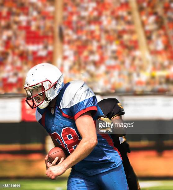 Football team's running back carries ball. Defender. Stadium fans. Field.