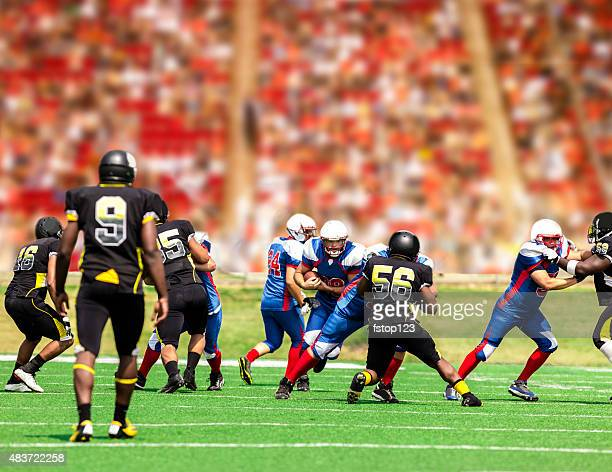 football team's running back carries ball. defenders. stadium fans. field. - high school football stock pictures, royalty-free photos & images