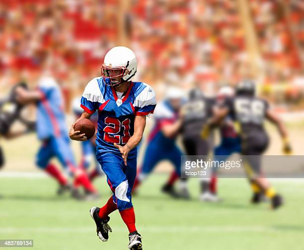 football team's running back carries ball. defenders. stadium fans. field. - wide receiver athlete stock pictures, royalty-free photos & images