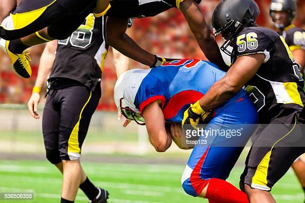 Football team's running back carries ball. Defenders. Stadium fans. Field.