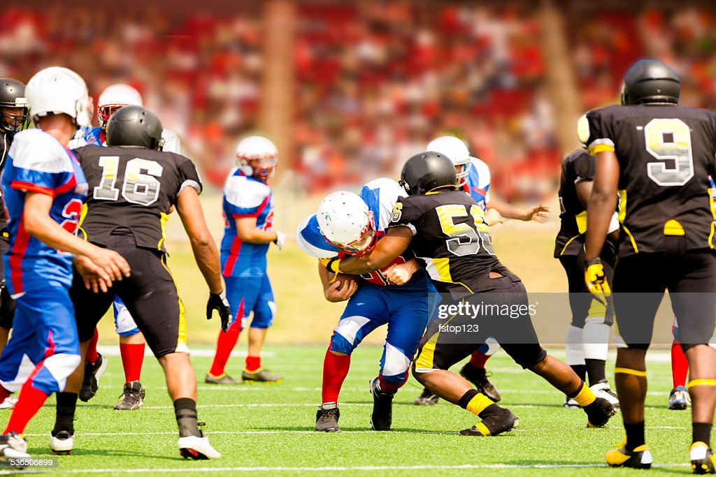 Football team's running back carries ball. Defenders. Stadium fans. Field. : Stock Photo