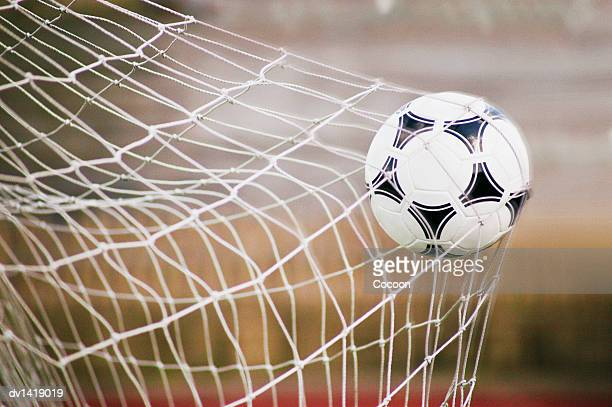 football trapped in a goal net, close-up - segnare foto e immagini stock