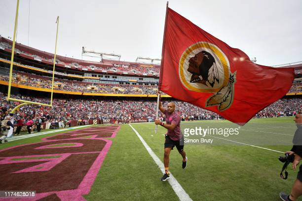 Washington Redskins cheerleader on field with flag with team logo before game vs New England Patriots at FedEx Field Landover MD CREDIT Simon Bruty
