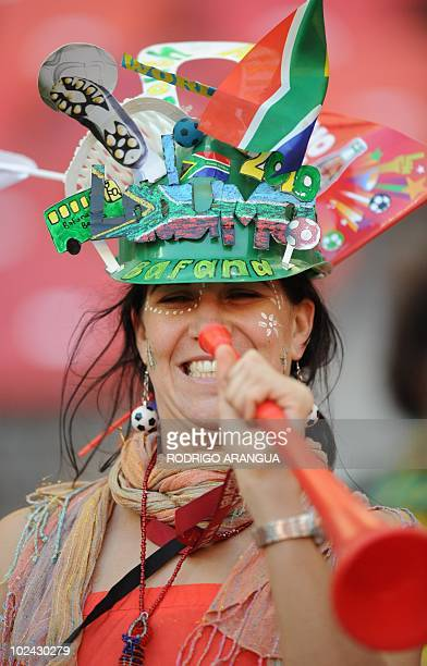 A football wearing a makarapa fan cheers with a vuvuzela before the start of the 2010 World Cup round of 16 football match between Uruguay and South...