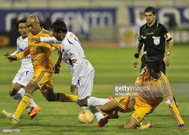 Footballer Abdon Reyes of Bolivia's San Jose vies for the ball with Hugo Ayala and Egidio Arevalo Rios of Mexico's Tigres during a Libertadores Cup...