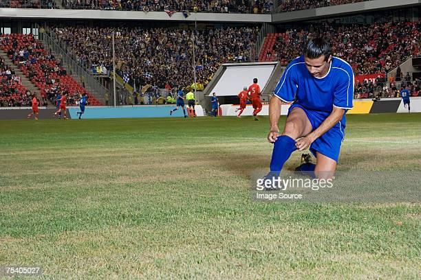 footballer adjusting sock - adjust socks stock pictures, royalty-free photos & images
