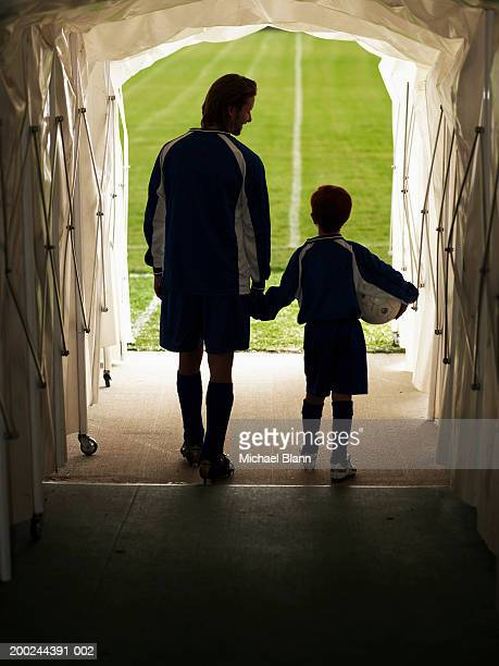 footballer and mascot (8-10) in tunnel leading to pitch, rear view - mascot stock pictures, royalty-free photos & images
