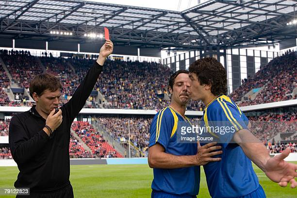 footballer arguing with a referee - referee stock photos and pictures