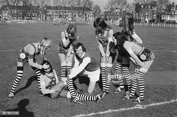 Footballer Bob McNab of Arsenal FC helps a group of models train for a charity football match UK 22nd February 1971