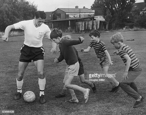 Footballer Bobby Robson practises some moves against a group of boys at the Fulham FC training ground at Ewell Surrey 8th August 1966