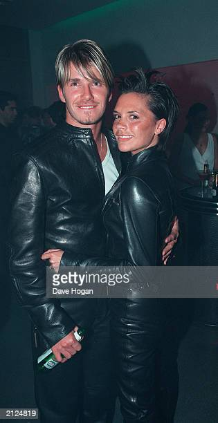 Footballer David Beckham and fiancee Spice Girl Victoria Adams pose in matching outfits at a party at the Versace store New Bond Street London on...