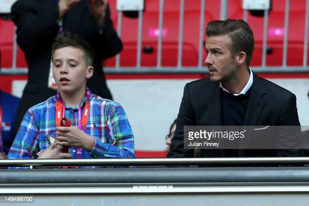 Footballer David Beckham and his son Brooklyn watch the Men's Football first round Group A Match between Great Britain and United Arab Emirates on...