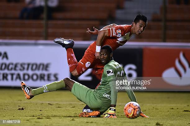 Footballer Fernando Uribe of Mexico's team Toluca scores past Ecuador's Liga de Quito goalkeeper Alexander Dominguez during their Libertadores Cup...