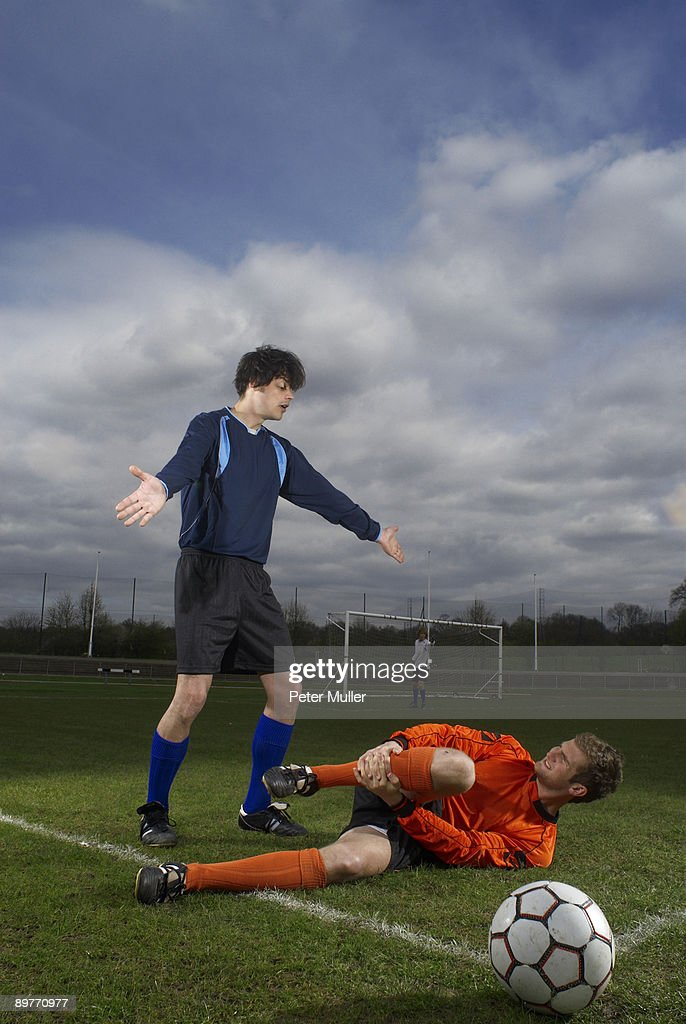 footballer fouled by another player : Stock Photo