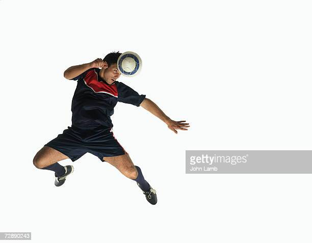 footballer heading ball in mid-air - ヘディングをする ストックフォトと画像