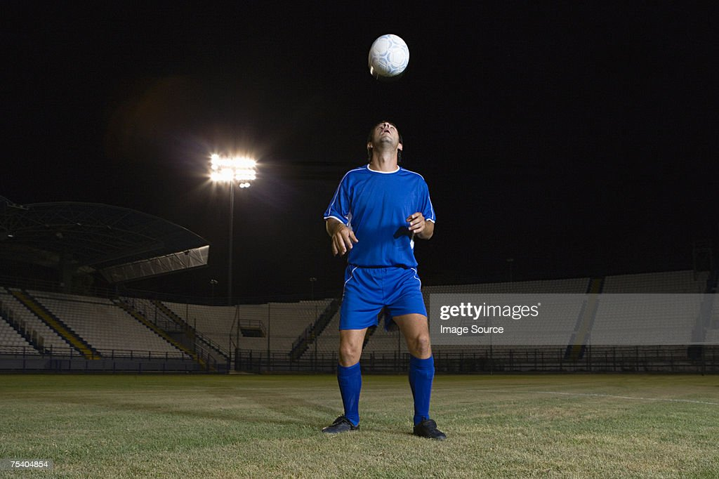 Footballer heading ball : Stock Photo