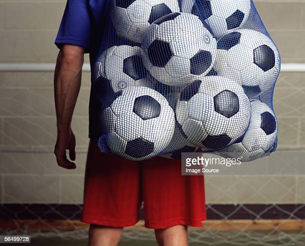 footballer holding a bag of footballs - bag stock photos and pictures