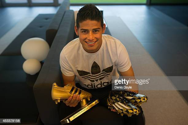 Footballer James Rodriguez holds his adidas Golden Boot Trophy and a pair of adiZero boots at Real Madrid's Valdebebas in recognition of scoring the...