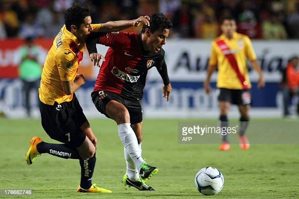 Footballer Jose Cardenas of Morelia and Omar Bravo of Atlas vie for the ball during their 2013 Mexican Apertura tournament match in Morelia on August...