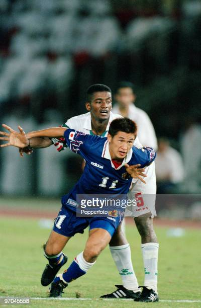 Footballer Kazuyoshi Miura of Japan is challenged by defender Hassan Mubarak, of the United Arab Emirates, in a qualifier for the 1998 FIFA World...