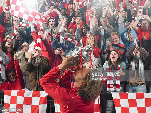 Footballer kissing trophy in front of cheering crowd