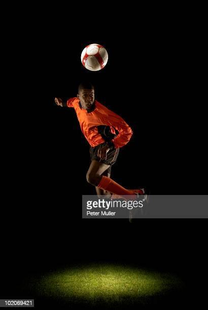 Footballer mid air heading ball