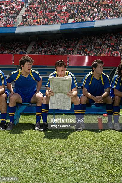 footballer reading a newspaper - reserve athlete stock pictures, royalty-free photos & images