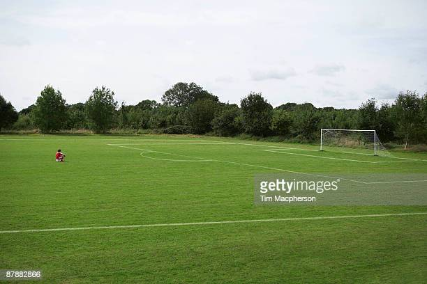 footballer sitting looking at the goal - football pitch stock pictures, royalty-free photos & images