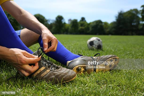 Footballer tying boot laces