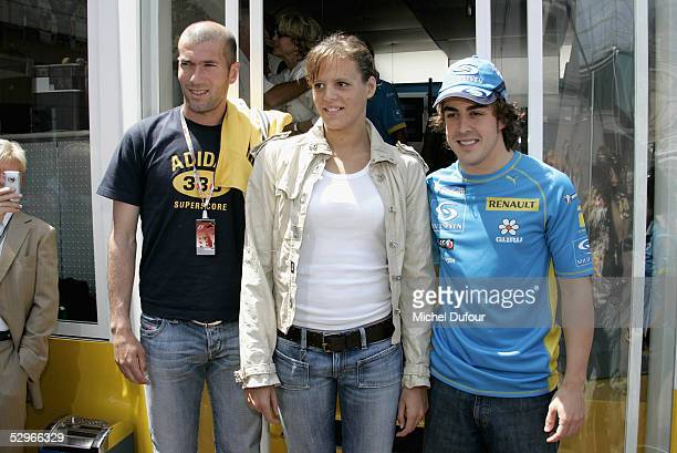 Footballer Zinadine Zidane poses with Lauren Manodou and Fernado Alonso before the start of the Monaco Gran Prix on May 22 2005 in Cannes France