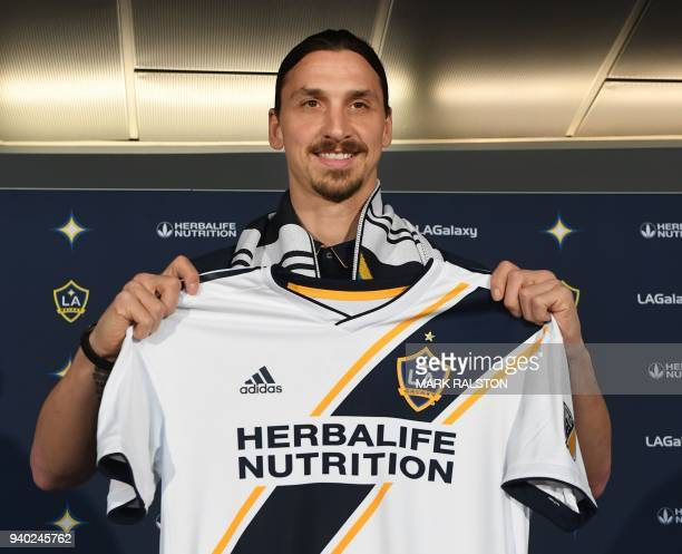 TOPSHOT Footballer Zlatan Ibrahimovic holds up a new team jersey for his new club LA Galaxy during a first press conference in Los Angeles California...