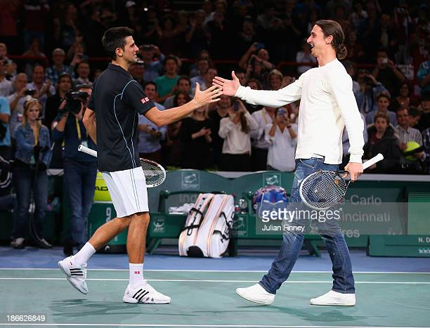 Footballer Zlatan Ibrahimovic shakes hands with Novak Djokovic of Serbia after a quick game after the match against Roger Federer of Switzerland...