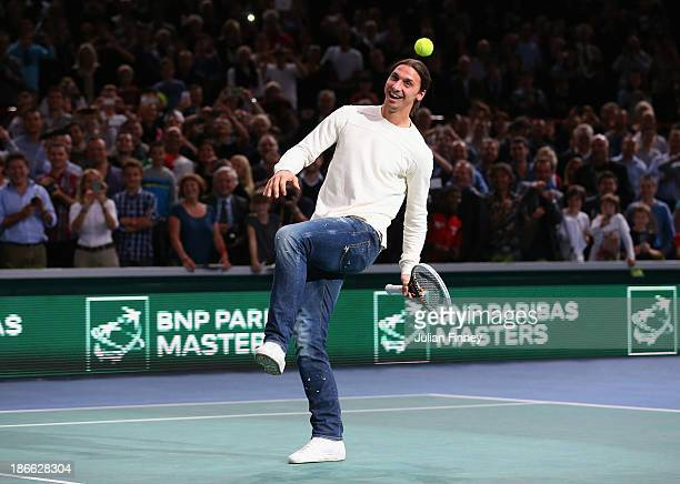 Footballer Zlatan Ibrahimovic swings and misses in a game with Novak Djokovic of Serbia after the match against Roger Federer of Switzerland during...