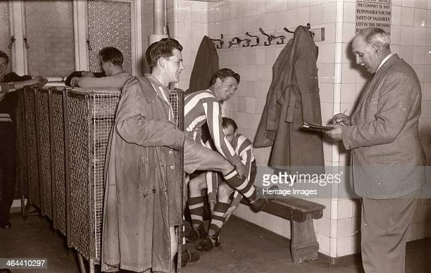 Footballers adjust their boots in the locker room 1953