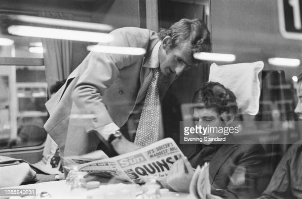 Footballers Alex Stepney and Brian Kidd of Manchester United FC reading 'The Sun' newspaper on a train, UK, 1971.