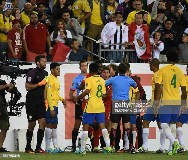 Footballers argue with Uruguayan referee Andres Cunha as he consults his assistants before awarding a goal to Peru during the Copa America Centenario...