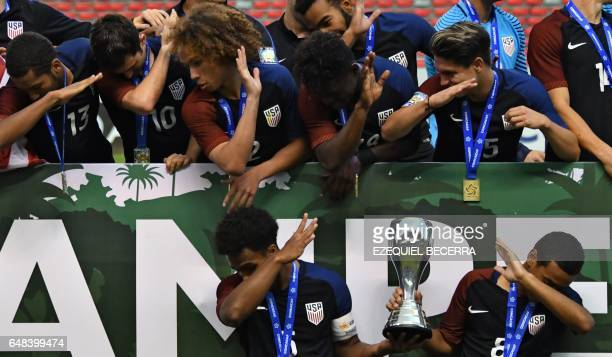 US footballers joke as they celebrate with the trophy after winning the U20 Concacaf final football match against Honduras at the National stadium in...