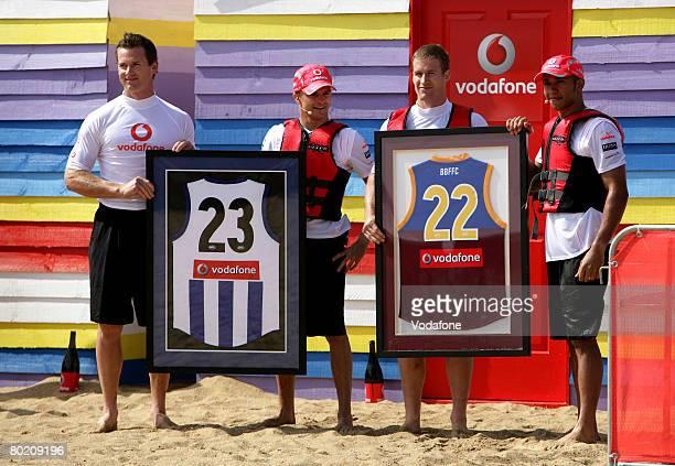 Footballers Luke Power, Adam Simpson pose for photos with Heikki Kovalainen and Lewis Hamilton of the Vodafone McLaren Mercedes before taking part in...