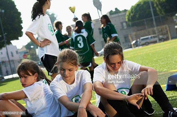 footballers (12-14) on pitch, other team celebrating in background - defeat stock photos and pictures