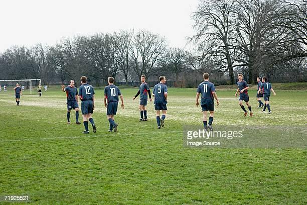 footballers on the pitch - équipe de football photos et images de collection