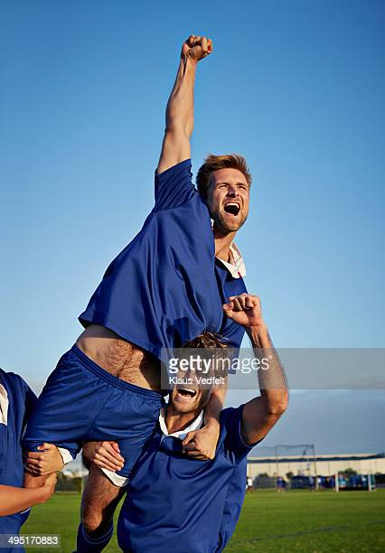 Footballplayer jumping with arm in air, after goal
