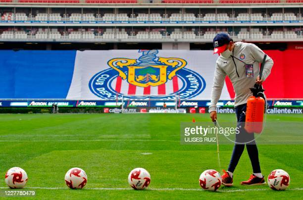 Footballs are disinfected before the beginning of a Mexican Apertura tournament football match between Guadalajara and Leon at the Akron stadium in...