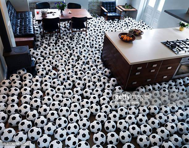Footballs covering floor of kitchen, elevated view