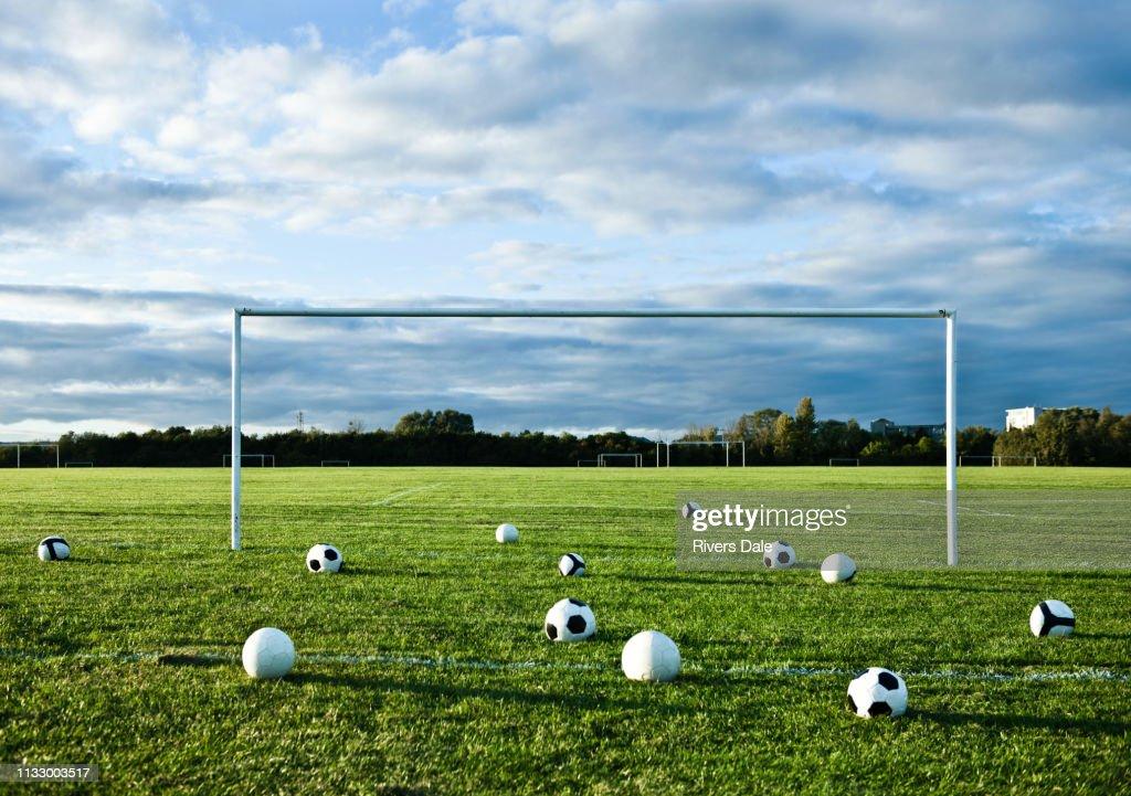 Footballs on empty pitch : ストックフォト