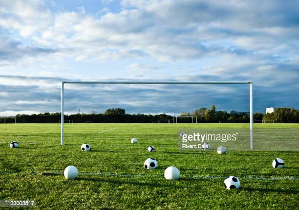footballs on empty pitch - soccer goal stock pictures, royalty-free photos & images