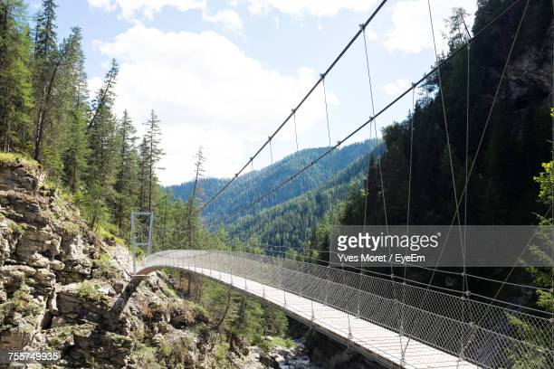 Footbridge Amidst Mountains Against Sky During Sunny Day