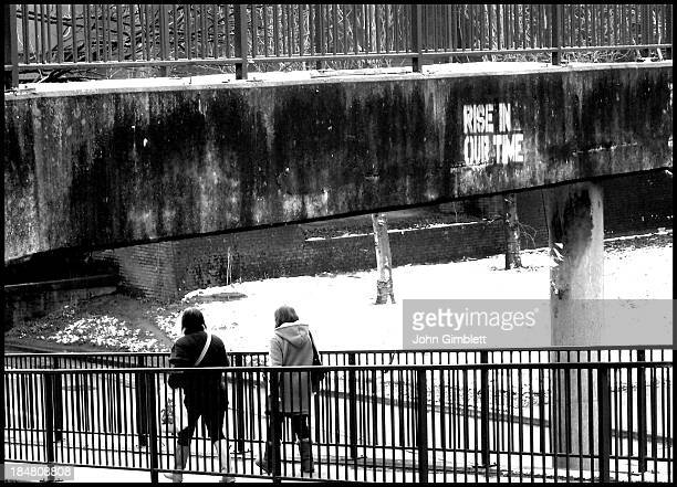 CONTENT] Footbridge in Newport South Wales with graffiti and people walking past Winter snow on the ground