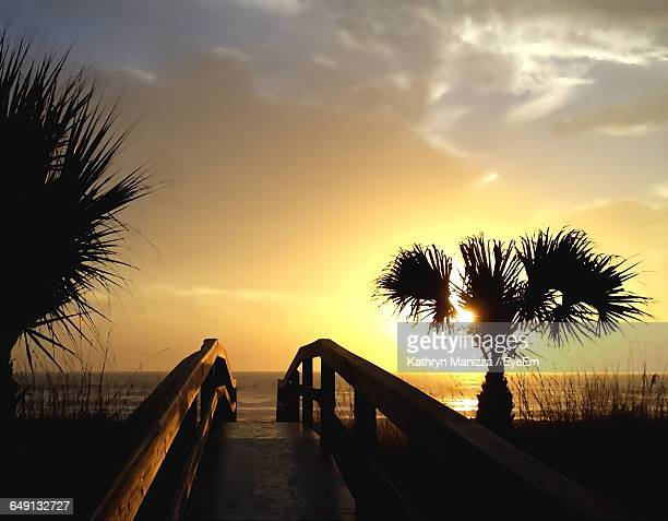 footbridge leading towards beach against sky during sunset - cocoa beach stock pictures, royalty-free photos & images